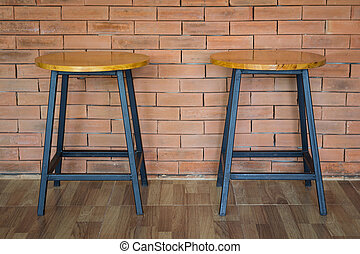 two wooden chairs on brick wall background