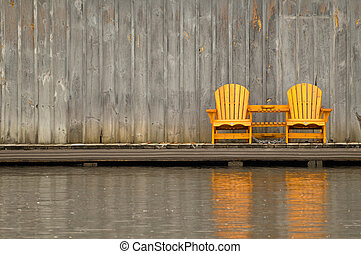 Two wooden Muskoka chairs against a wall
