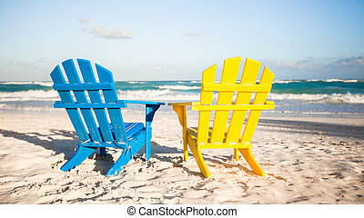 Two wooden chairs: yellow and blue on a white sandy beach,...