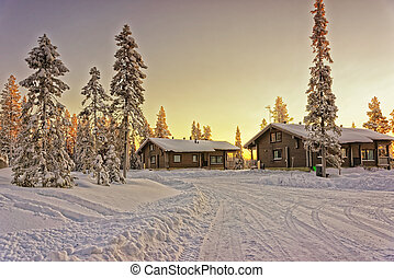 Two wooden cottages at winter finnish Lapland