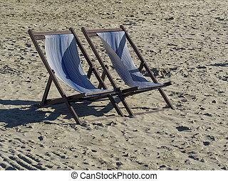 two wooden deck chair on a sandy beach