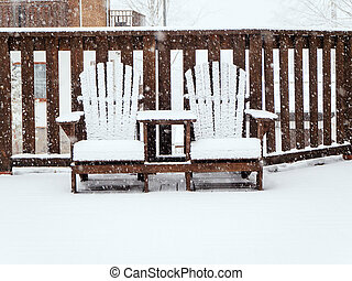 Two wooden garden chairs sit on a terrace covered with snow in winter during snowfall