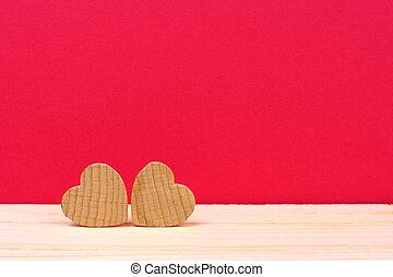 Two wooden hearts against a red background