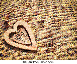 Two wooden decorative hearts on sackcloth, canvas background. Vintage style.
