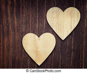 Two wooden hearts placed nicely on a vintage wood background