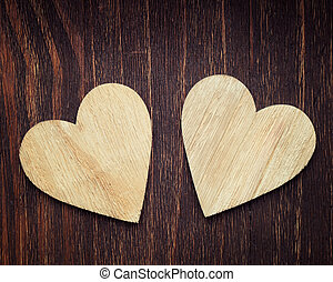 Two wooden hearts placed nicely on a vintage wood backrgound
