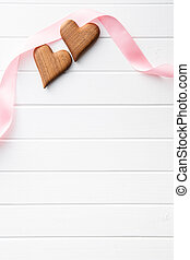 Two wooden hearts with pink ribbon.