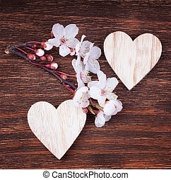 Two wooden hearts with spring cherry blossom flowers on a vinta