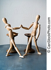 Two wooden human figures standing on a table shake hands