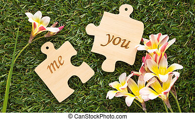 Two wooden puzzle pieces with word me and you, with flowers on green grass