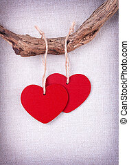 Two wooden red hearts hanging on a tree branch on vintage background