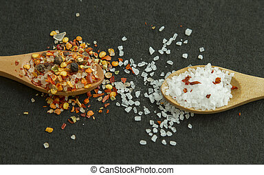 Two wooden spoons with spices and salt on black background