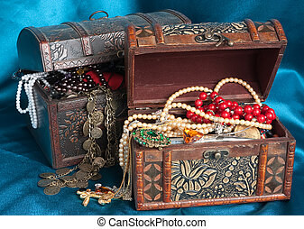 Two wooden treasure chests with valuables on blue textile