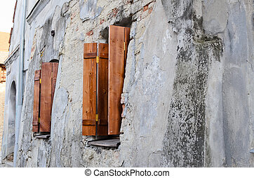 Two wooden windows on an old degraded wall