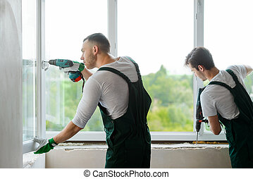 Two workers are mounting a window in the house. Men are using a screwdriver and a rotary drill.
