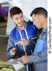 two workers are talking while holding papers