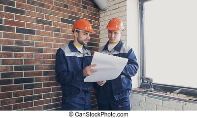two workers at building site with blueprints