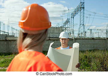 two workers at electrical power station