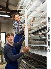 Two workers choosing PVC window profile