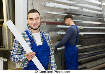 Two workers choosing PVC window profile - Two...