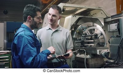 Two workers discussing a project in front of CNC lathe...