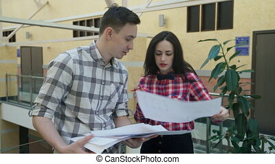 Two workers discussing business project standing in office