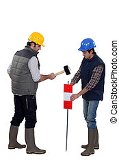Two workers hammering sign into the ground