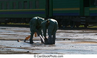 Two Workers In Protective Clothes Rolling Water Hose - This...