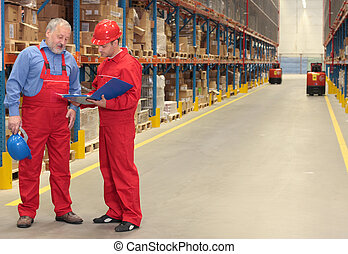 two workers in uniforms in warehouse. one is older, one is younger, different activities.