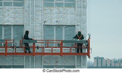 Two workers lifting up on the building for continue constructing. Mid shot
