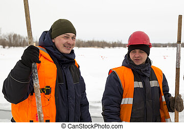 Two workers on the ice of a frozen pond