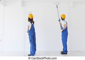 Two workers painting the wall