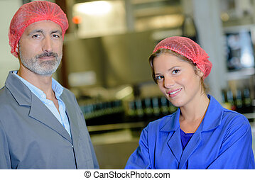 two workers posing in factory