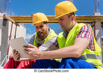 Two workers reading online information or watching a video during break