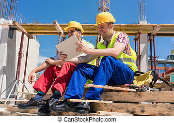 Two workers reading online information or watching a video on a