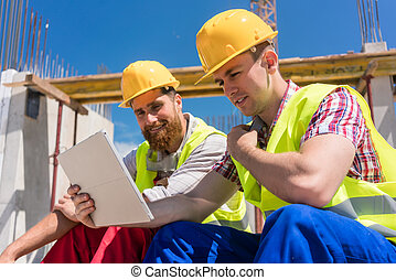 Two workers reading online information or watching a video
