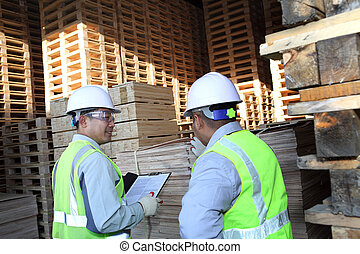 two workers talking beside on stacking pallet with holding...