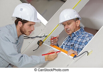two workers using spirit level on window opening