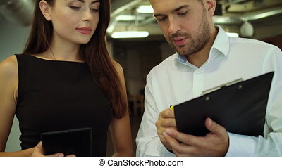 Two workers using tablet and notebook in the office.