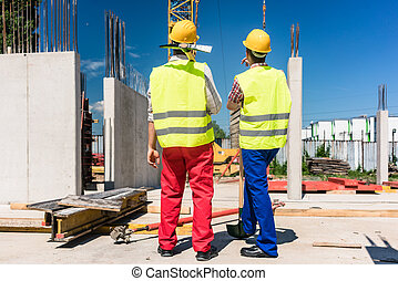 Two workers wearing safety equipment while planning work