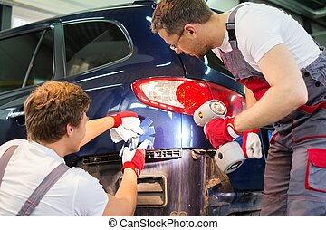 Two workers with colour samples choosing correct shade in a car body workshop