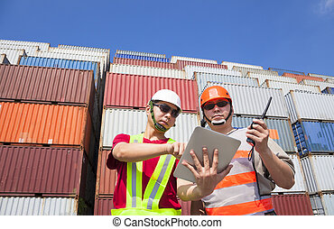 two workers with tablet and standing before stack of containers