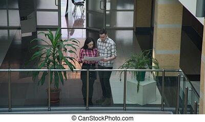 Two workers woman man discussing business project standing in hall