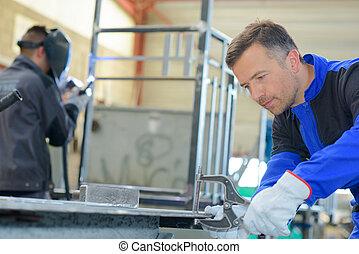 Two workmen busy in workshop