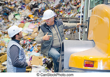 two workmen in recycling center