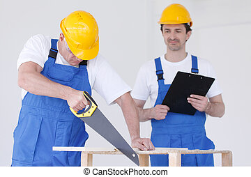 Two workmen with saw and folder