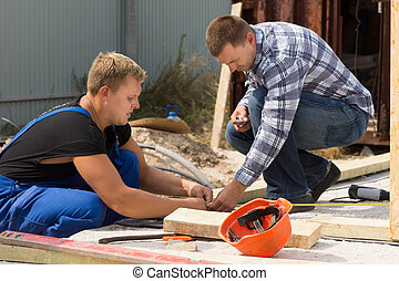 Two workmen working on a building site measuring insulation...