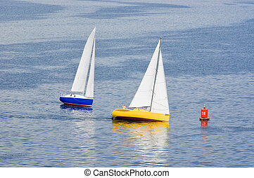 Two yacht making a turn near buoy on a summer river