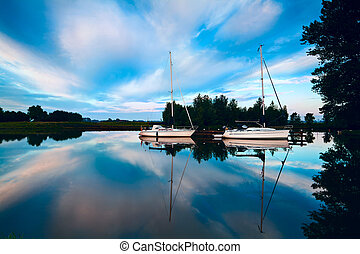 two charming yachts on river in morning and sky reflection
