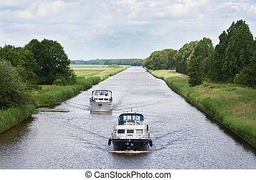 Two yachts sailing in a straight Dutch canal